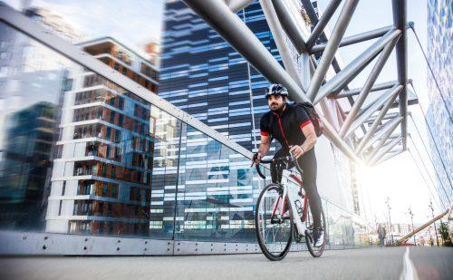sprek mann med skjegg og ryggsekk sykler over Akrobaten bro på Oslo S